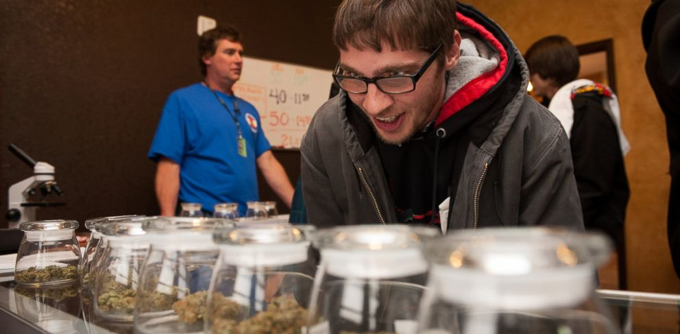 PHOTO: Tyler Williams of Blanchester, Ohio selects marijuana strains to purchase at the 3-D Denver Discrete Dispensary on January 1, 2014 in Denver, Colo.