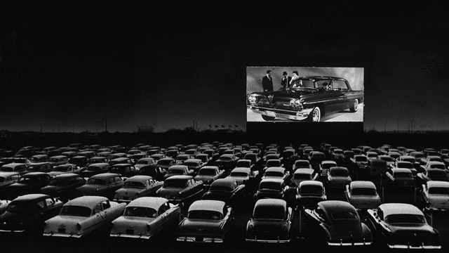PHOTO: Vehicles fill a drive-in theater while people on the screen stand near a new car, 1950s.