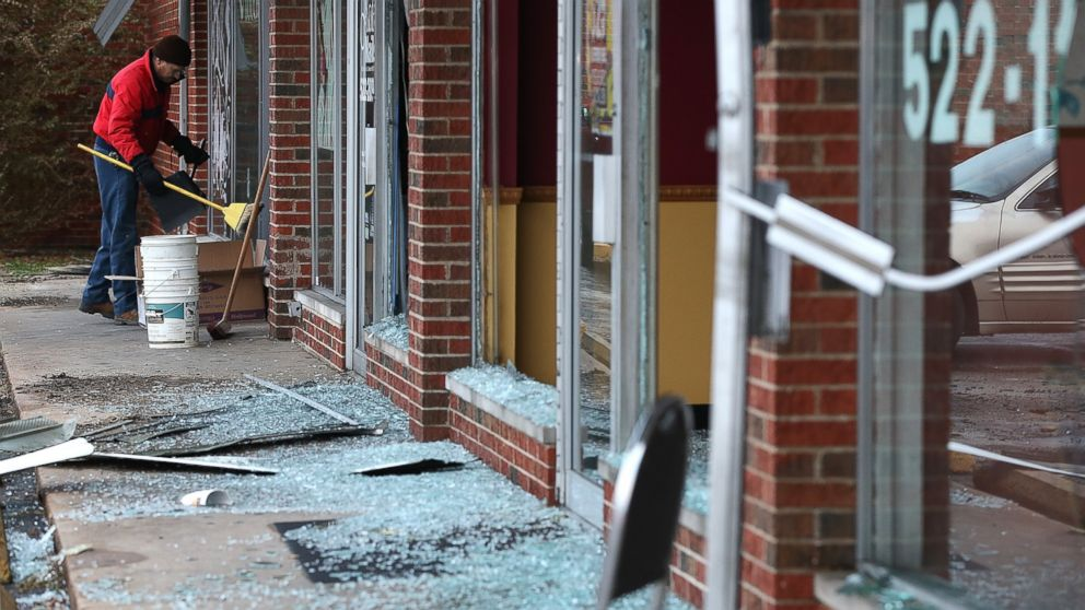 A worker cleans up glass at a building that was damaged during a demonstration on Nov. 25, 2014 in Dellwood, Mo. Demonstrators caused extensive damage in Ferguson and surrounding areas last night after a St. Louis County grand jury decided to not indict Ferguson police Officer Darren Wilson in the shooting of Michael Brown.
