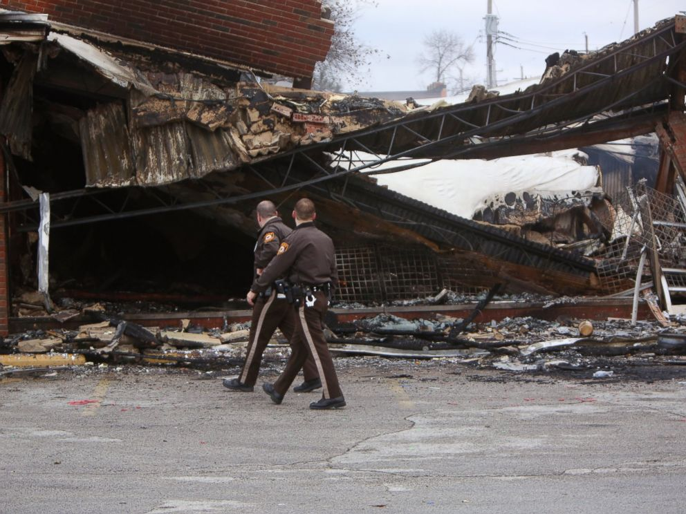 PHOTO: Police officers walk past the smoldering remains of a beauty supply store at the corner of Chambers Road and West Florissant Avenue, Nov. 25, 2014, in Ferguson, Mo.