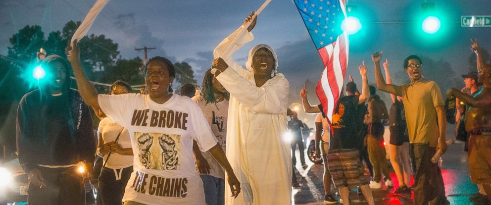 PHOTO: Demonstrators marking the one-year anniversary of the shooting of Michael Brown march along West Florrisant Street on Aug. 9, 2015 in Ferguson, Mo.