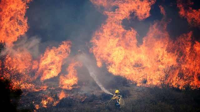 PHOTO: A Forestry fire fighter fights a wall of fire during an out of control wildfire, May 2, 2013 in Camarillo, Calif.