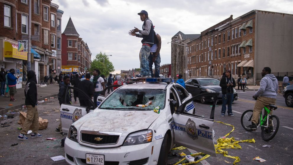 People stand on a police car during a protest for Freddie Gray in Baltimore, April 27, 2015.
