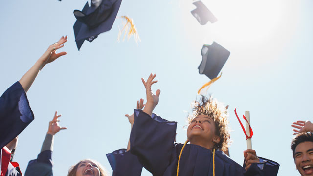 PHOTO: High school graduates are seen tossing caps into the air, after their graduation ceremony.