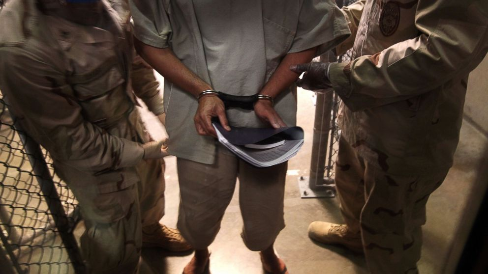 U.S. Navy guards escort a detainee in the Guantanamo Bay detention center, March 30, 2010, in Guantanamo Bay, Cuba.