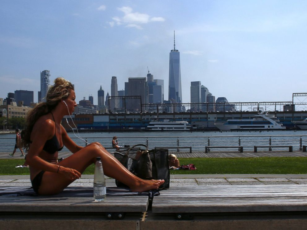 PHOTO: A woman sunbathes as the temperature in New York feels like 100 degrees, July 25, 2016.