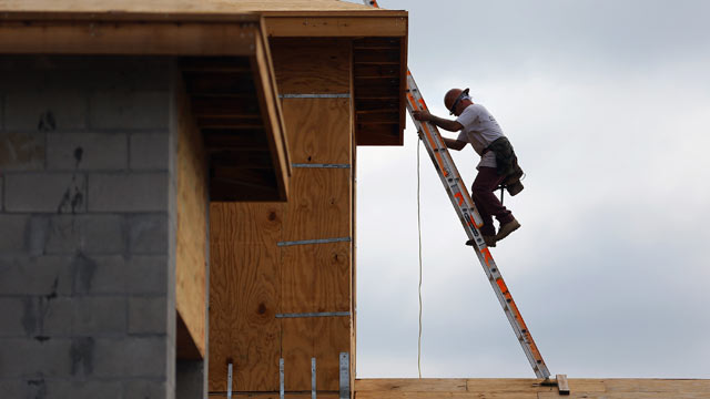 PHOTO: A construction worker climbs on the roof of a home as he helps build a Toll Brothers Inc. home in the Azura community on November 20, 2012 in Boca Raton, Florida.