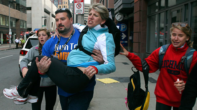 PHOTO: Former New England Patriots player Joe Andruzzi carries a woman from the scene on Exeter Street after two explosions went off near the finish line of the 117th Boston Marathon, April 15, 2013.