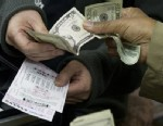 PHOTO: A customer purchases Powerball lottery tickets for the estimated record 425 million USD jackpot prize, Powerballs biggest winnings ever, at a convenience store in Washington on November 26, 2012.