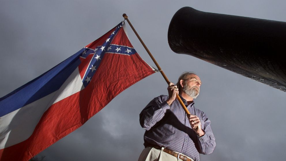In this file photo taken on Dec. 12, 2001, Harry Sharp proudly holds the Mississippi State flag in the centre of Vicksberg Miss.