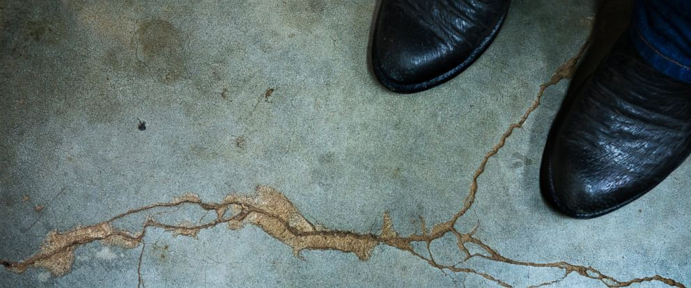 PHOTO: Gary Landra stands on a crack across his basement floor that he says was caused by an earthquake four years ago in Prague, Okla., on Jan. 25, 2015.