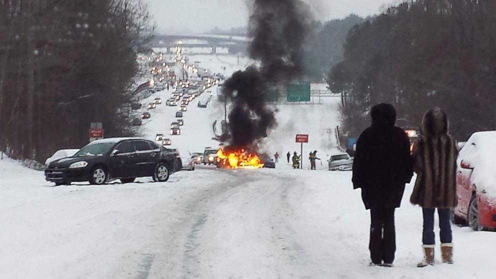 Motorists watch a vehicle burn after it caught fire while struggling to get up a snow covered hill in Raleigh, North Carolina on February 12, 2014.