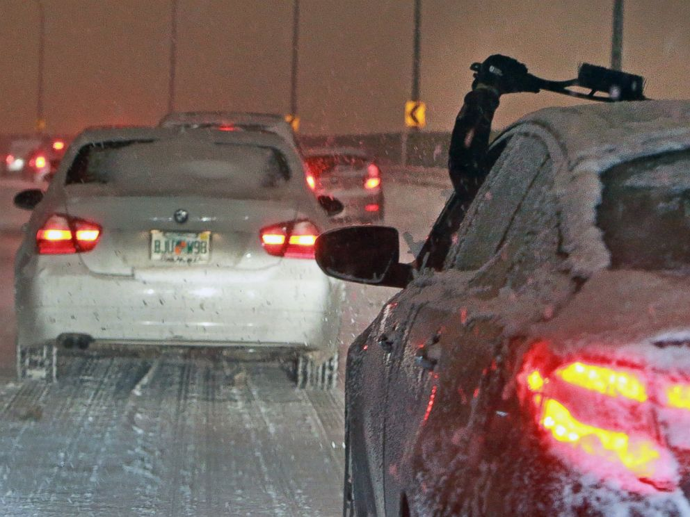 A driver reaches out to clear their windshield of snow and ice while navigating storm snarled traffic in Boston on Dec. 17, 2013.