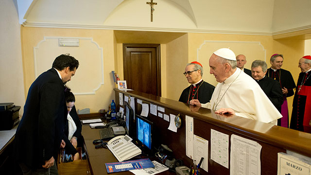 PHOTO: This handout picture released by the Press office shows Pope Francis at the reception desk of the Domus Internationalis Paulus VI residence as he pays the bill of his stay before the conclave, March 14, 2013, in Rome.