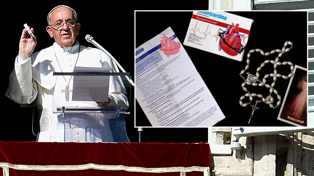 """PHOTO:Pope Francis showcontaining a rosary during his Sunday Angelus prayer from the window of his apartment overlooking St.-Peter's square at the Vatican. The pope recommended the rosary as medicine that """"does goo"""