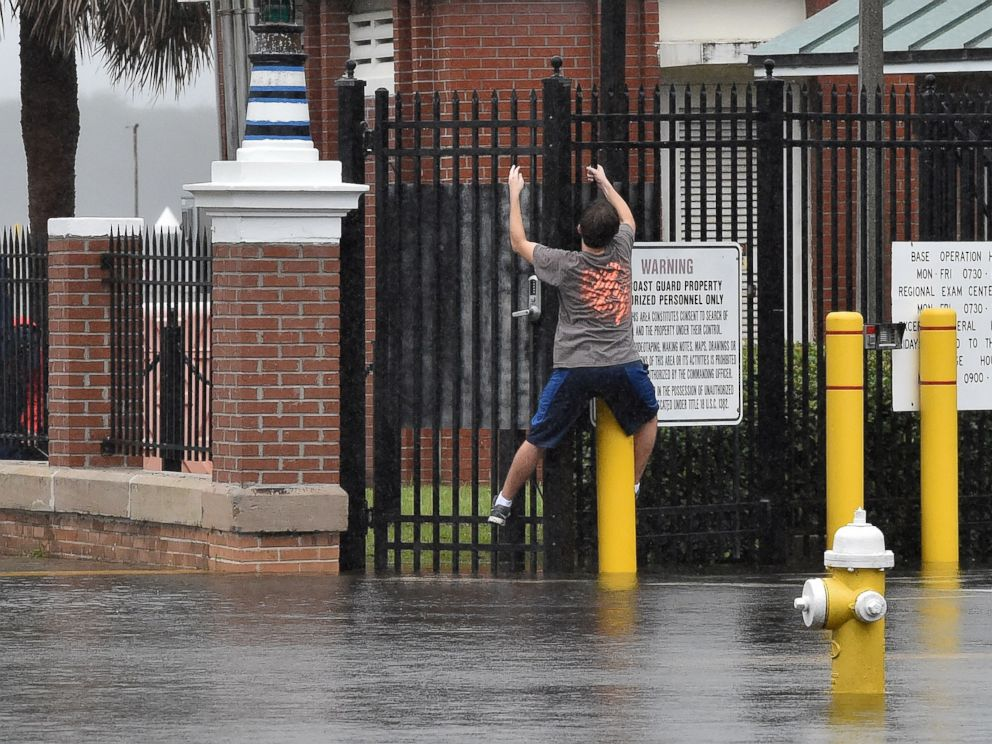 PHOTO: A boy tries to stay on dry by climbing along a fence on a flooded street in downtown Charleston, South Carolina on Oct. 4, 2015.