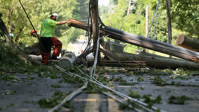 PHOTO: Workers cut up a fallen tree, so that power lines can be repaired, on June 30, 2012 in Huntington, Maryland.