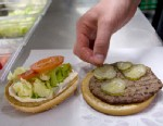 PHOTO: An employee places a pickle in a whopper burger at a Burger King restaurant.