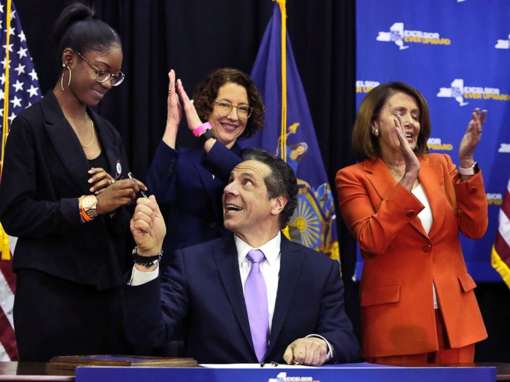 PHOTO: New York Gov. Andrew Cuomo hands a pen to Marjory Stoneman Douglas High School student Aalayah Eastmond, left, as he signs a bill at John Jay College of Criminal Justice, that removes guns from domestic abusers, May 1, 2018, in New York.