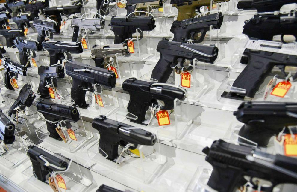 PHOTO: Guns lie in a booth during a gun show.