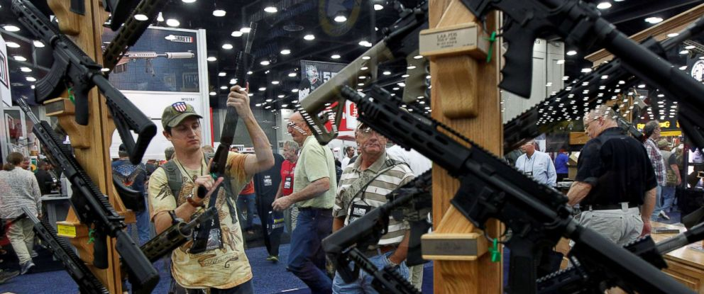 PHOTO: Gun enthusiasts look over Rock River Arms guns at the National Rifle Associations (NRA) annual meetings and exhibits show in Louisville, Kentucky, May 21, 2016.