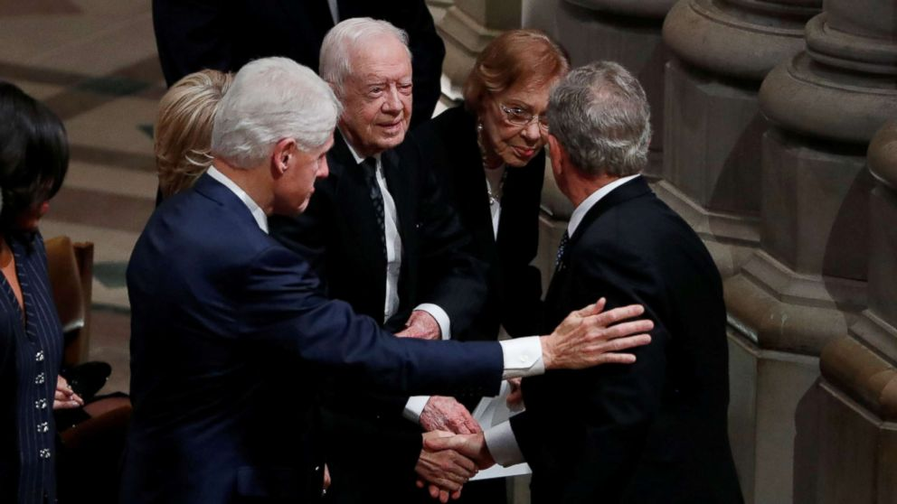 Former President George W. Bush greets former President Bill Clinton, former President Jimmy Carter and former first lady Rosalynn Carter as he arrives at the state funeral for his father, former President George H.W. Bush at the Washington National Cathedral, Dec. 5, 2018.