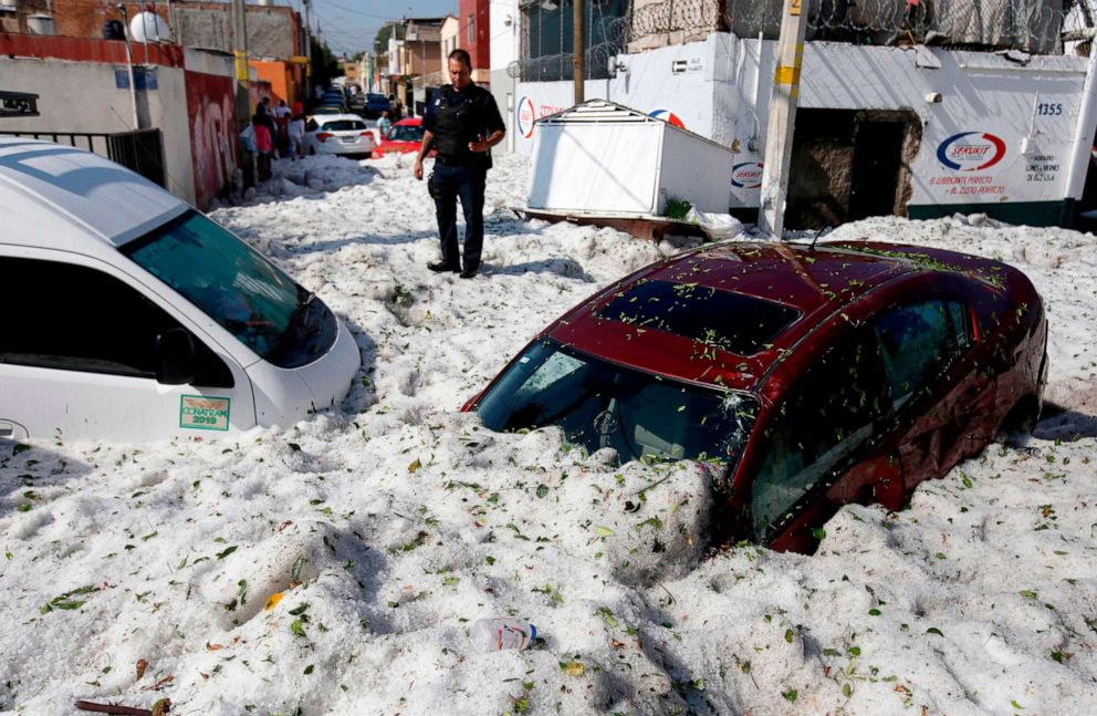 PHOTO: A policeman stands next to vehicles buried by hail in the eastern area of Guadalajara, Jalisco state, Mexico, June 30, 2019.