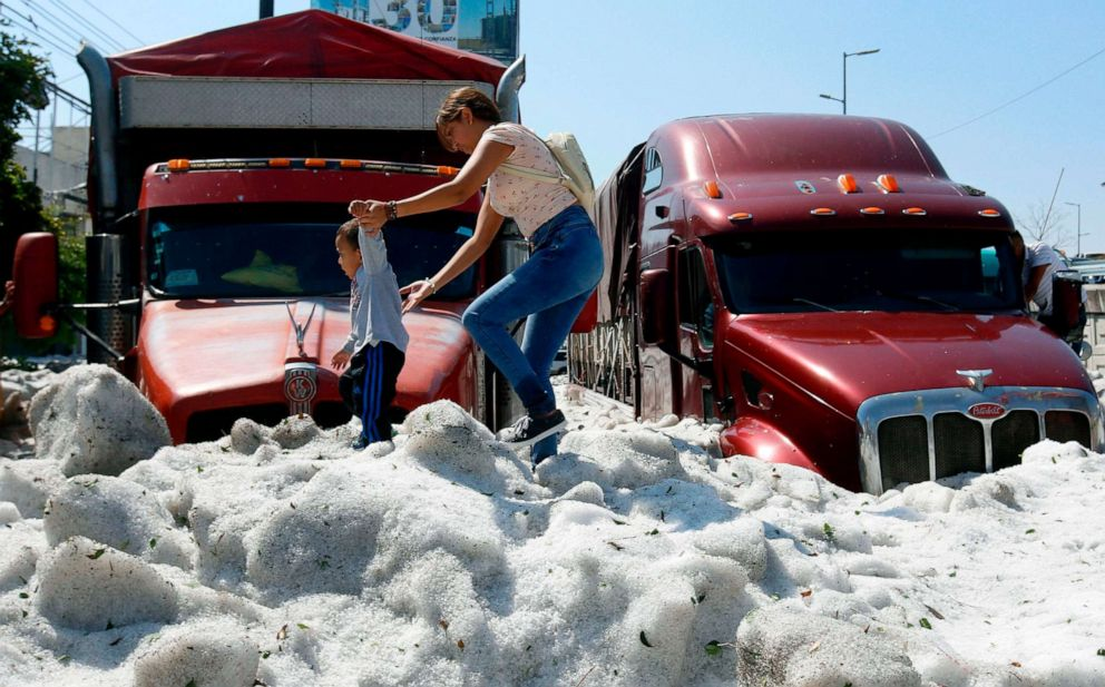 PHOTO: A woman and a child walk over hail in the eastern area of Guadalajara, Jalisco state, Mexico, June 30, 2019.