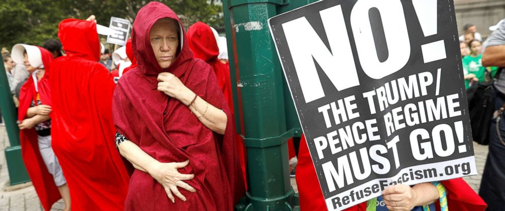 """PHOTO: Women dressed in red gowns as worn in the """"Handmaids Tale"""" protest outside the Department of Homeland Security (DHS) Cybersecurity Summit where U.S. Vice President Mike Pence, July 31, 2018, in Manhattan, New York City."""