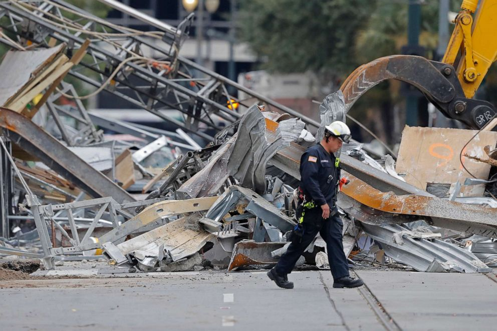 PHOTO: A worker walks in front of rubble in the street at the site of the Hard Rock Hotel in New Orleans, Oct. 16, 2019.