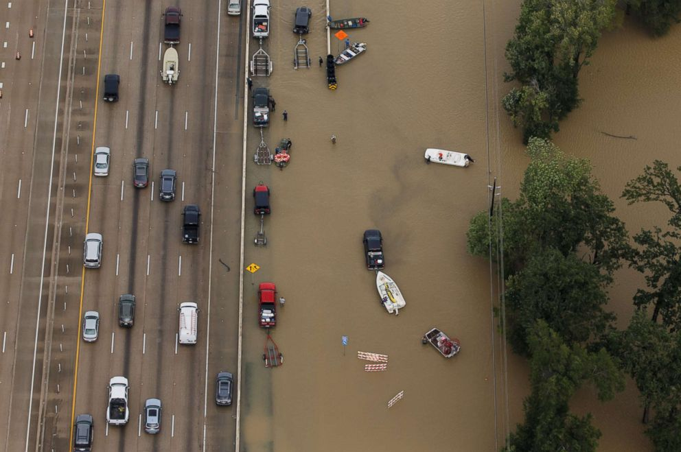 PHOTO: Vehicles sit on Interstate 10 which was closed due to high water, as volunteers launch rescue boats into the flooded waters, Aug. 29, 2017, in Houston, Texas.