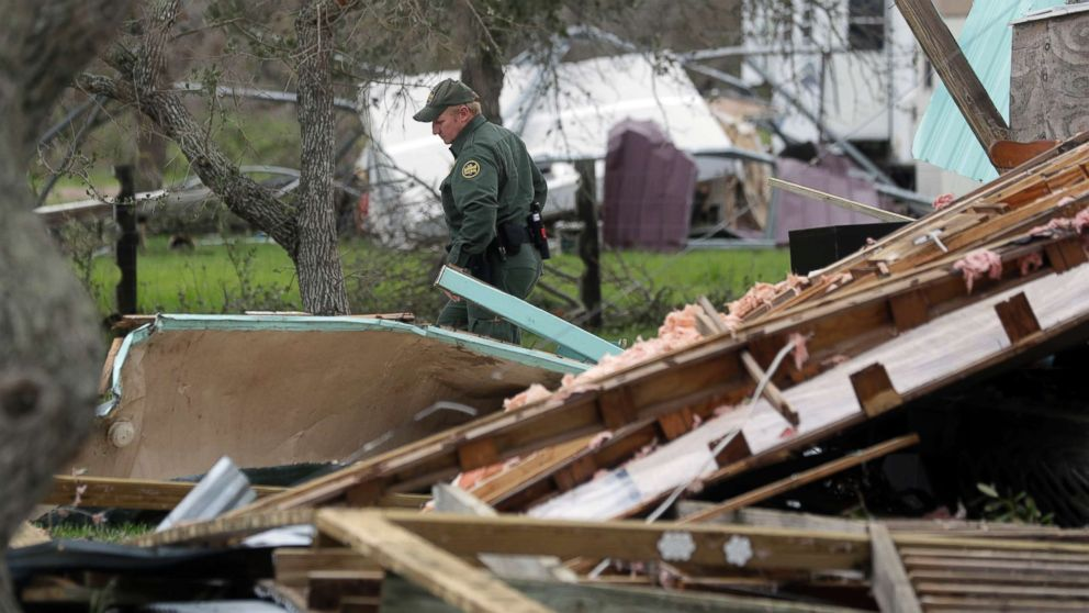 An official looks through debris as he checks a home damaged by Hurricane Harvey, Sunday, Aug. 27, 2017, in Rockport, Texas.
