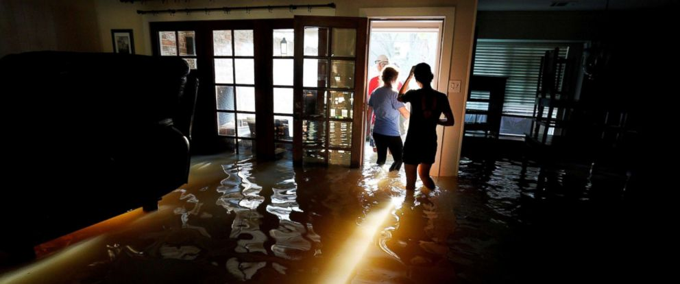 PHOTO: A family moves belongings from their home flooded by Harvey in Houston, Texas, Aug.t 31, 2017.