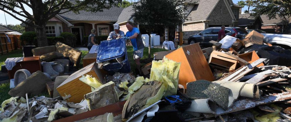 PHOTO: Members of the Olson family remove debris and damaged items from their fathers home in the Twin Oaks Estate after Hurricane Harvey caused widespread flooding in Houston, Aug. 31, 2017.