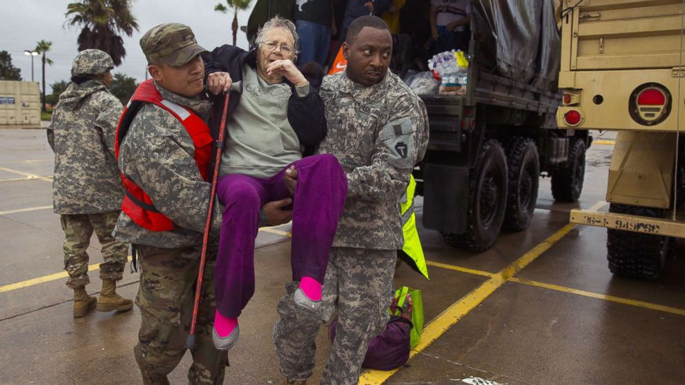 Texas Army National Guard members Sergio Esquivel, left, and Ernest Barmore carry 81-year-old Ramona Bennett after she and other residents were rescued from their Pine Forest Village neighborhood due to high water from Harvey, Aug. 29, 2017 in Houston, Texas.