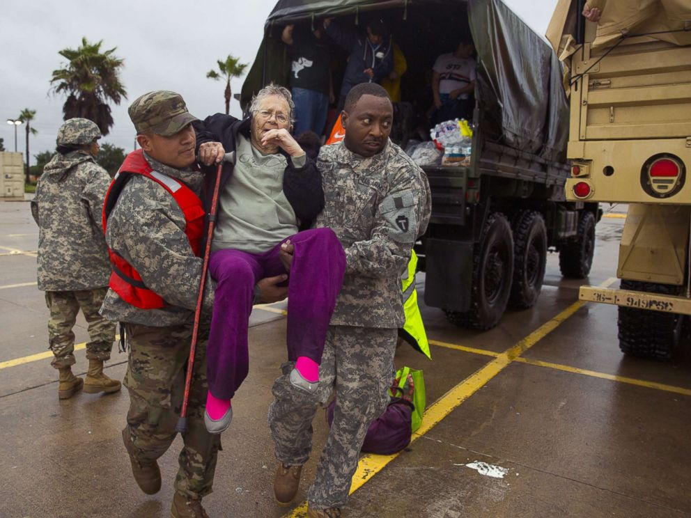 PHOTO: Texas Army National Guard members Sergio Esquivel, left, and Ernest Barmore carry 81-year-old Ramona Bennett after she was rescued, Aug. 29, 2017 in Houston, Texas.