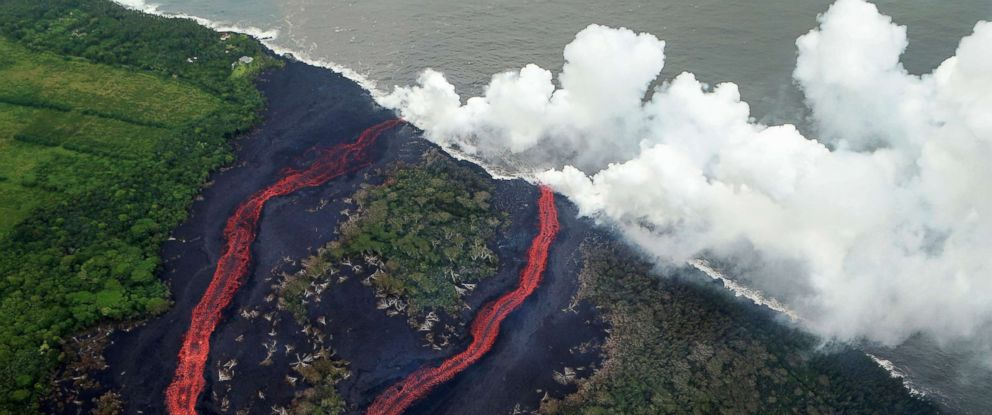 PHOTO: Steam plumes rise as lava enters the Pacific Ocean, after flowing to the water from a Kilauea volcano fissure, on Hawaiis Big Island, May 21, 2018, near Pahoa, Hawaii.