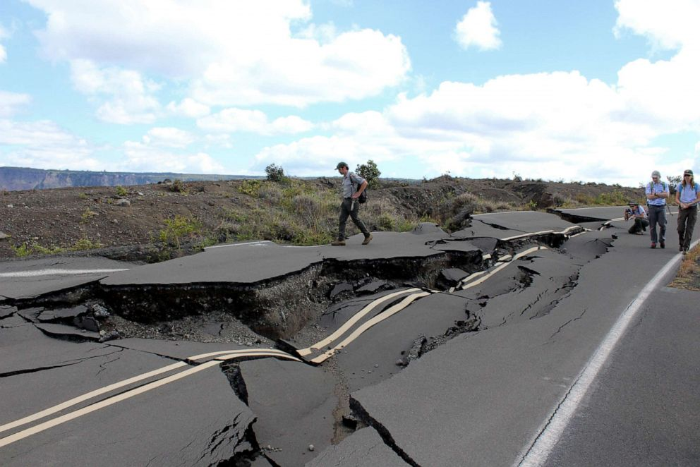 PHOTO: Tourists walk around a road damaged by earthquakes in Hawaiis Volcanoes National Park.