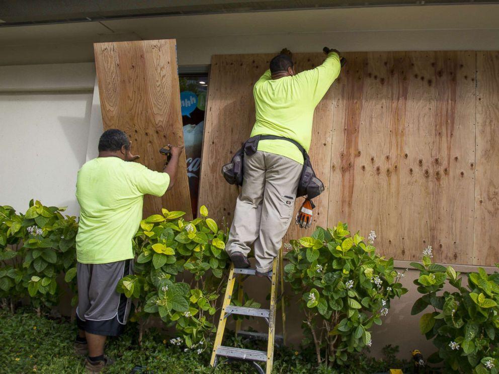 PHOTO: Yamasaki Construction workers, Talbot Khakai, left, and David Halafihi board up McDonalds multiple plate glass windows in preparation for Hurricane Lane on Aug. 22, 2018 in Honolulu.