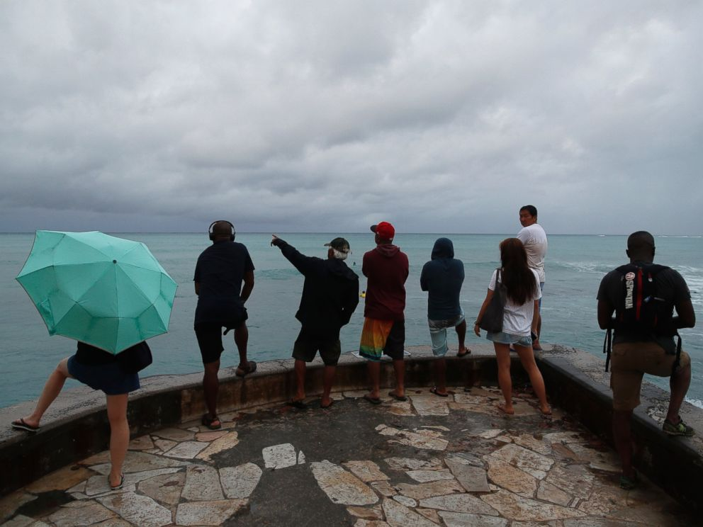 People look out over the ocean along Waikiki Beach in a light rain from Tropical Storm Lane, Saturday, Aug. 25, 2018, in Honolulu..
