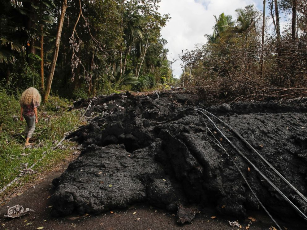 Hannique Ruder, a 65-year-old resident living in the Leilani Estates subdivision, walks past the mound of hardened lava while surveying the neighborhood Friday, May 11, 2018, near Pahoa, Hawaii.