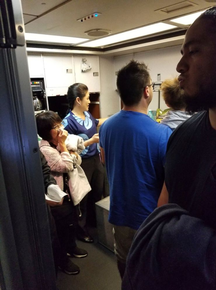 This Friday, Aug. 31, 2018 photo provided by Nicholas Andrade shows people gathered in a back galley on a Hawaiian Airlines flight from Oakland, Calif., to Kahului, Hawaii, after a can of pepper spray went off inside the plane.