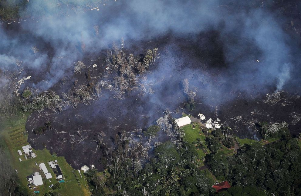PHOTO: Lava from volcanic fissures overtakes structures and trees in the Leilani Estates neighborhood in the aftermath of eruptions from the the Kilauea volcano on Hawaiis Big Island on May 6, 2018 in Pahoa, Hawaii.