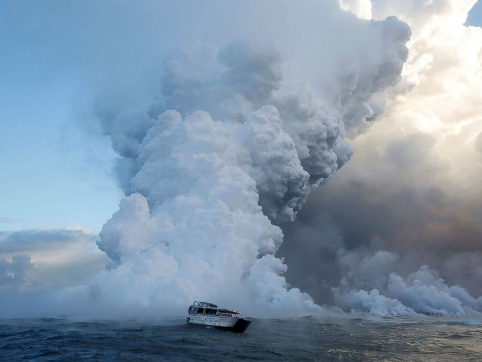 PHOTO: People watch from a tour boat as lava flows into the Pacific Ocean in the Kapoho area, east of Pahoa, during ongoing eruptions of the Kilauea Volcano in Hawaii, June 4, 2018.