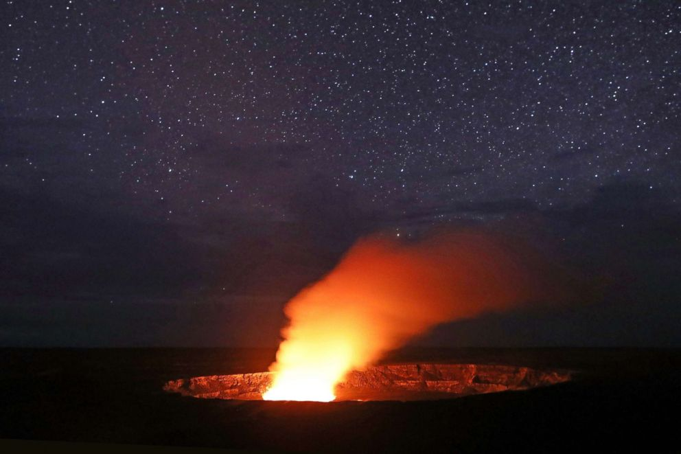 PHOTO: Stars shine above as a plume rises from the Halemaumau crater, illuminated by glow from the craters lava lake, within the Kilauea volcano summit at the Hawaii Volcanoes National Park, May 9, 2018, in Hawaii Volcanoes National Park, Hawaii.