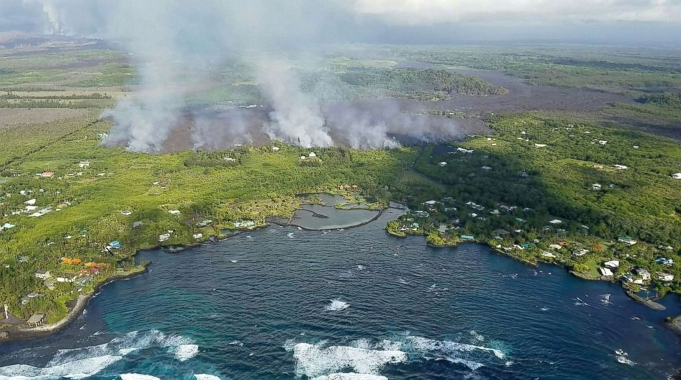 PHOTO: Fumes and lava flow from Kilauea Volcano on Hawaiis Big Island towards the ocean in an image taken from a helicopter on June 3, 2018.