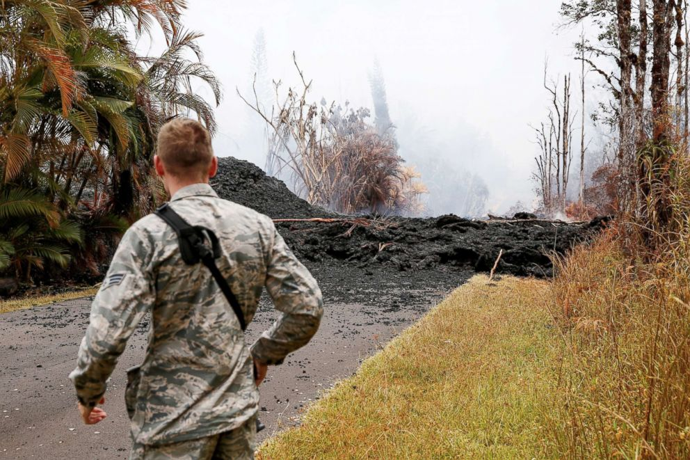 PHOTO: Senior Airman John Linzmeier, of the Hawaii National Guard, observes a lava flow in the Leilani Estates subdivision during ongoing eruptions of the Kilauea Volcano in Hawaii, May 13, 2018.