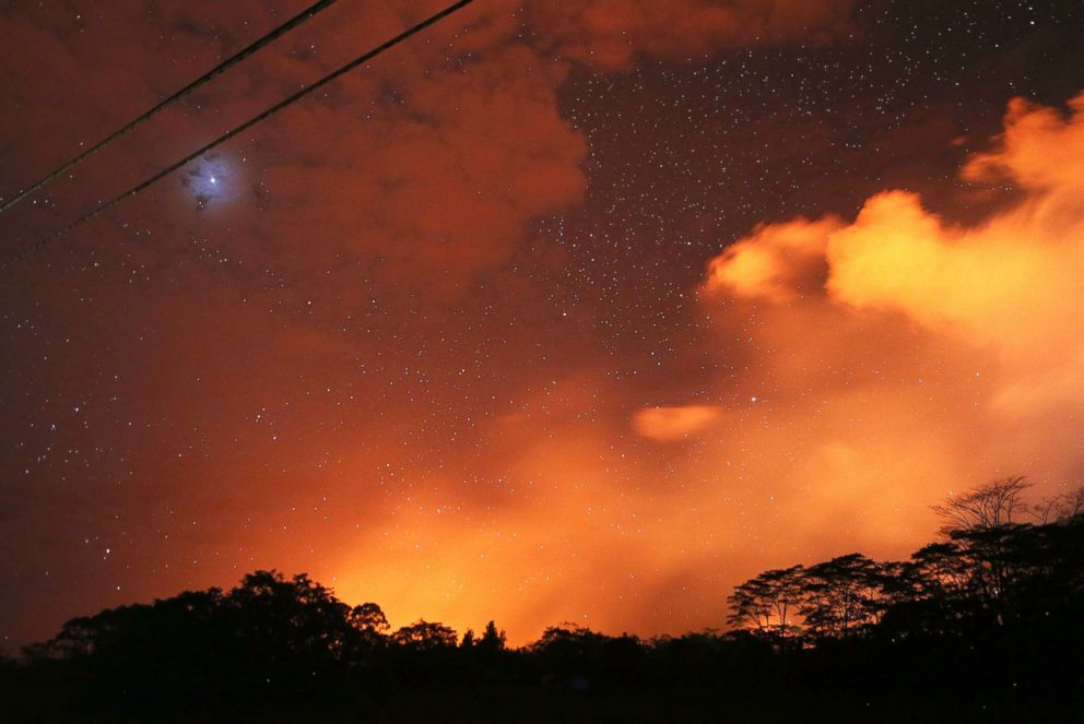 PHOTO: Lava from active fissures illuminates volcanic gases from the Kilauea volcano as stars shine on Hawaiis Big Island, May 15, 2018, in Hawaii Volcanoes National Park, Hawaii.