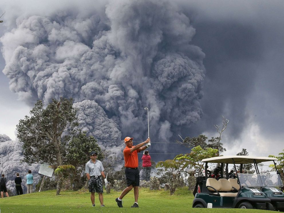 PHOTO: People play golf as an ash plume rises in the distance from the Kilauea volcano on Hawaiis Big Island, May 15, 2018, in Hawaii Volcanoes National Park, Hawaii.