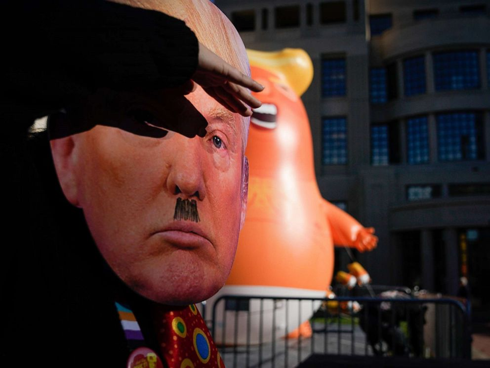 PHOTO: A protester wearing a mask dances near a Baby Trump balloon last week in front of the courthouse on November 4, 2019 in Lexington, Kentucky. (Photo by Bryan Woolston/Getty Images)